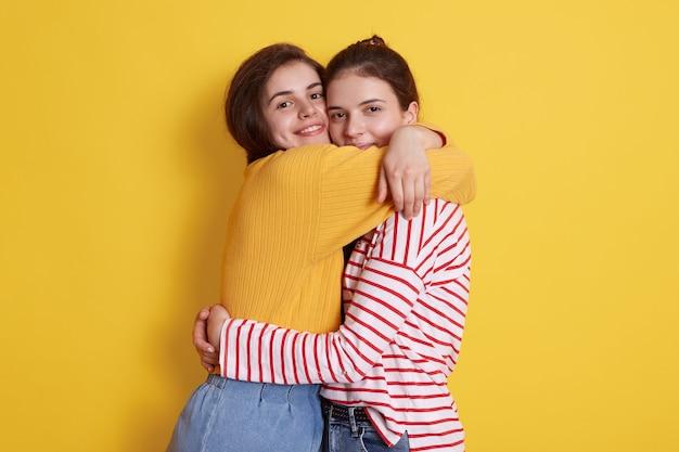 Twee europese jonge mooie donkerharige dames huggind geïsoleerd op geel