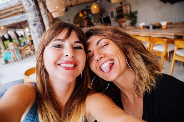 Twee europese kaukasische vrouw vrienden met natuurlijke make-up en kort haar nemen selfie in zomerterras