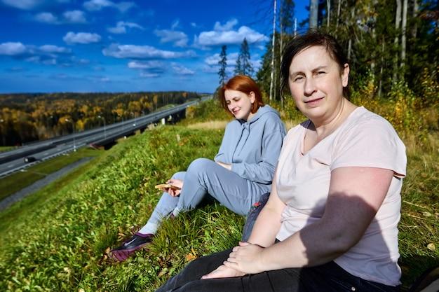Twee europese vrouwen in sportkleding zitten in het herfstbos in de buurt van de snelweg.