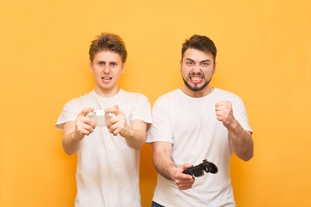 Twee expressieve gamers die videogames spelen met joysticks in hun handen op geel