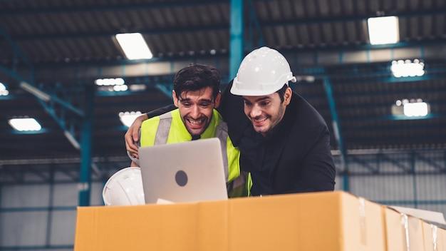 Twee fabrieksarbeiders vieren succes samen in de fabriek of het magazijn. industrie werk prestatie concept.