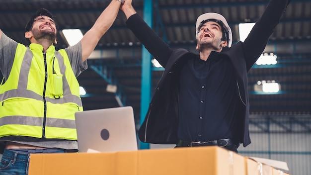 Twee fabrieksarbeiders vieren succes samen in de fabriek of het magazijn