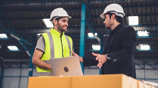 Twee fabrieksarbeiders werken en bespreken productieplan in de fabriek. industrie en technisch concept.