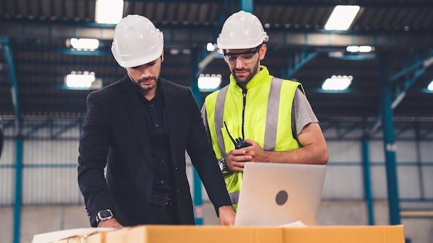 Twee fabrieksarbeiders werken en bespreken productieplan in de fabriek
