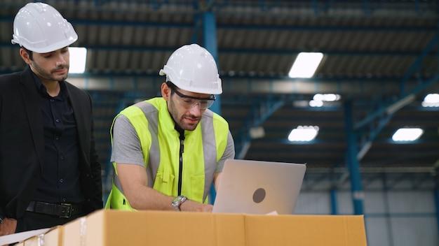 Twee fabrieksarbeiders werken en bespreken productieplan in de fabriek.