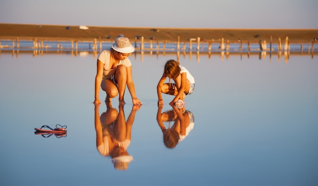 Twee fantastisch mooie meisjes in ongewone outfits op een prachtig transparant zoutmeer zoeken iets in een glanzend oppervlak