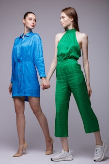 Twee fashion modellen in het kort blauwe kleding schoenen groene jumpsuit sneakers mooie jonge vrouwen