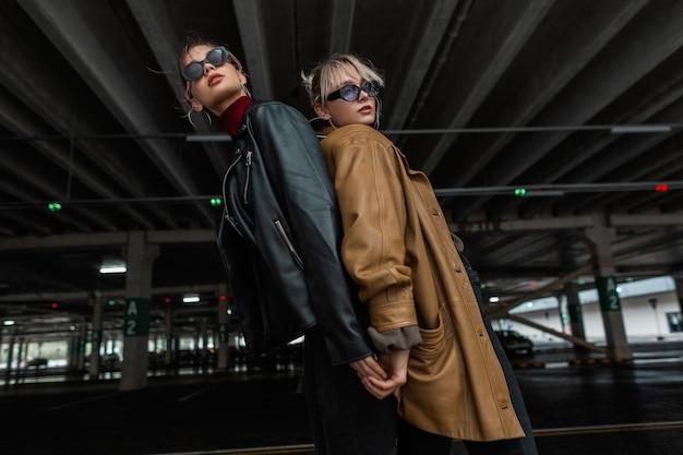 Twee fashion modellen meisjes in stijlvolle stadskleding met een leren jas met coole zonnebril poseren in de buurt van een parkeerplaats in de stad
