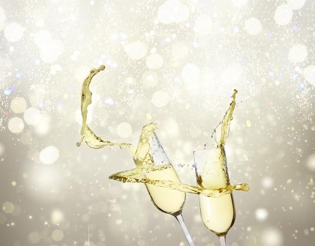 Twee feestelijke champagneglazen op zilveren bokehachtergrond met lichten