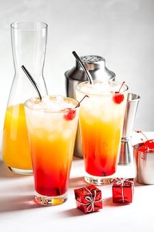 Twee feestelijke cocktails van tequila sunrise op een grijze betonnen achtergrond naast dozen met geschenken