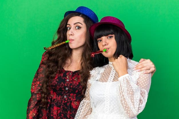 Twee feestvrouwen die een feestmuts dragen en feesthoorn blazen