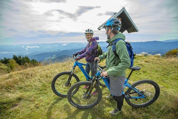 Twee fietsers rusten uit op een top van een berg
