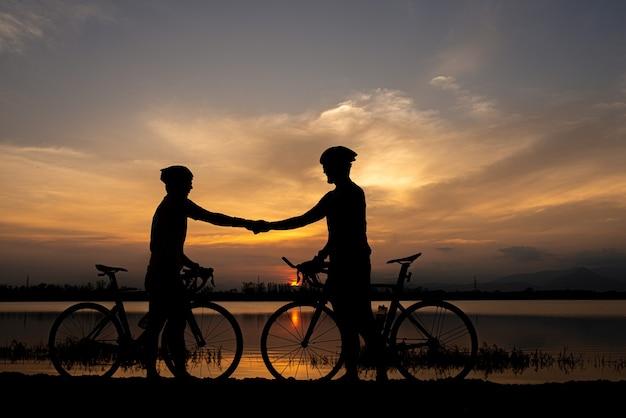 Twee fietsers schudden hand na finish samen fietsen. sportiviteit concept.
