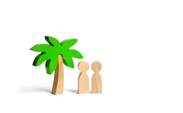 Twee figuren van mensen onder een palmboom
