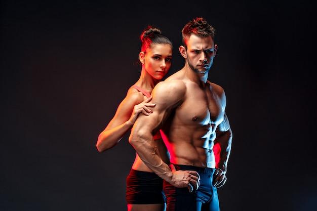 Twee fit sporters samen poseren, dicht bij elkaar.