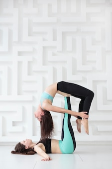 Twee fitte jonge vrouwen doen acro yoga pose in de buurt van witte muur