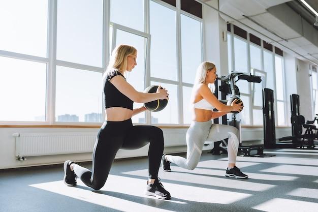 Twee fitte vrouwen doen squats met medicijnbal in lichte sportschool op zonnige dag. gewichtsverlies, persoonlijke training.