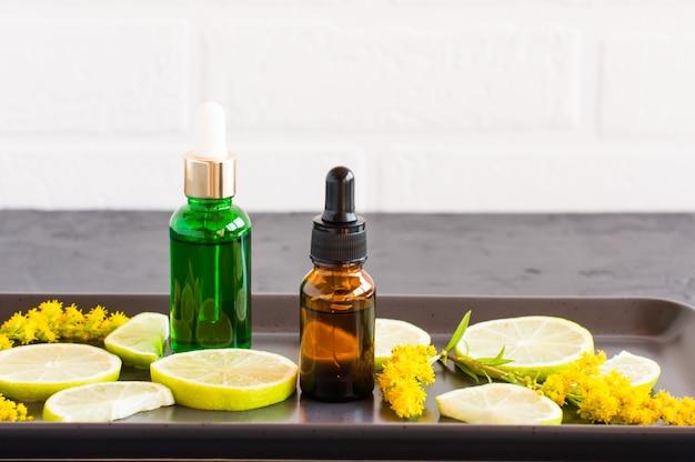 Twee flesjes met een pipet met een cosmetisch product gemaakt van citroen en limoen voor gezichts- en lichaamsverzorging. cosmetica van natuurlijke aard.