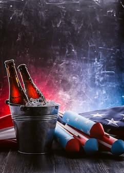 Twee flessen bier in een ijsemmer met de amerikaanse vlag in de buurt en raketten voor vuurwerk. onafhankelijkheidsdag viering concept