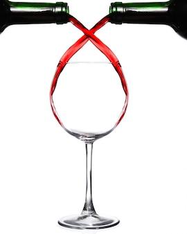Twee flessen die rode wijn in één glas gieten