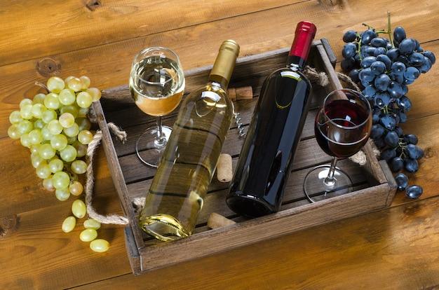 Twee flessen en glazen met rode en witte wijn en druiven op een houten ondergrond. bovenaanzicht.