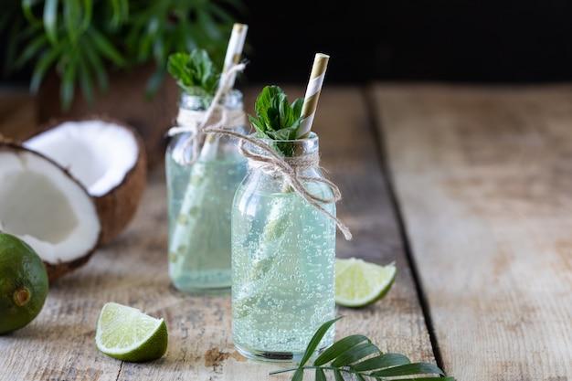 Twee flessen kokoswater met munt en limoen op een houten tafel. vegetarisch drankje. mojito. kopieer ruimte
