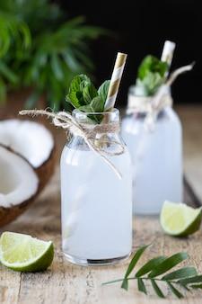 Twee flessen kokoswater op een houten lijst.