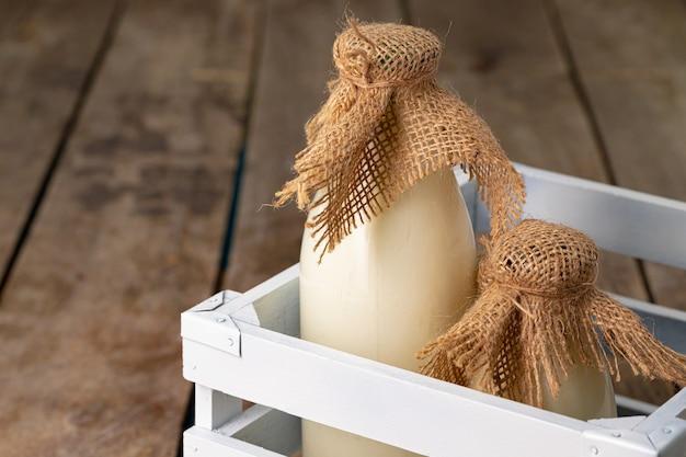 Twee flessen melk in houten doos op houten achtergrond close-up