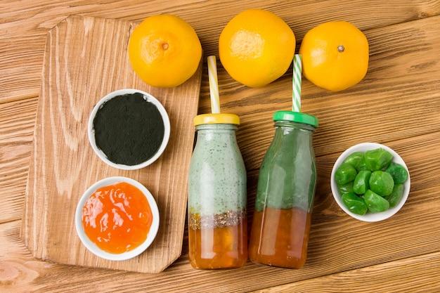 Twee flessen met spirulina smoothie en jam op een houten achtergrond. bijna droge kumquat en algenpoeder