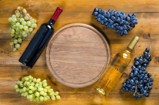 Twee flessen rode en witte wijn, een tros druiven en een ronde snijplank. bovenaanzicht, kopieer ruimte, plat gelegd.