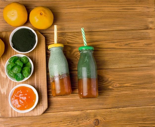 Twee flessen smoothie met spirulina op een houten achtergrond.
