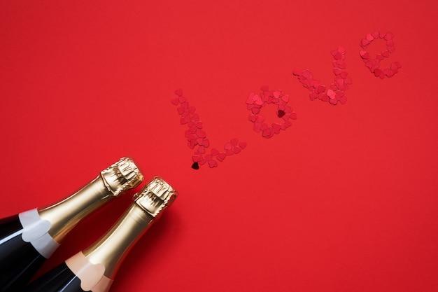 Twee flessen van champagne met harten vormden confettien die woordliefde op rode achtergrond vormen.