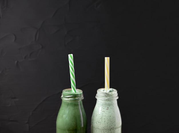 Twee flessen van groene smoothie gemaakt van spirulina en yoghurt op een zwarte achtergrond.