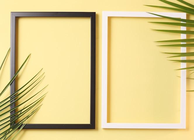Twee fotoframe en palmbladeren op pastel gele achtergrond