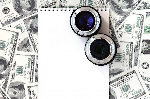 Twee fotografische lenzen en een wit notitieboekje liggen op de achtergrond van heel wat dollarrekeningen. ruimte voor tekst