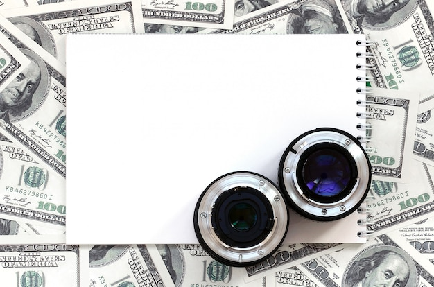 Twee fotografische lenzen en een wit notitieboekje liggen op de achtergrond