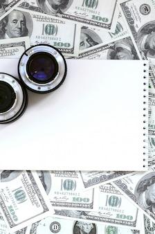 Twee fotografische lenzen en witte notebook