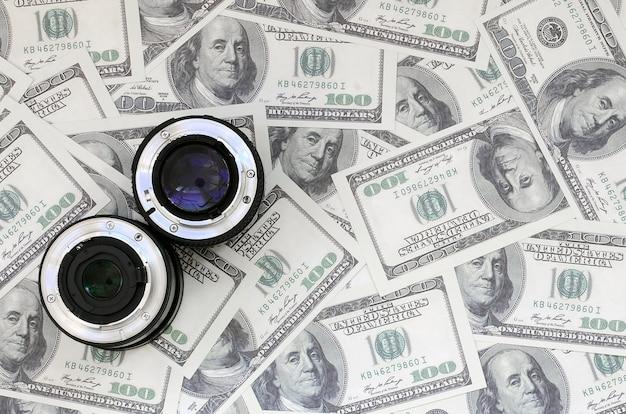 Twee fotografische lenzen liggen op de achtergrond van heel wat dollarrekeningen. ruimte voor tekst