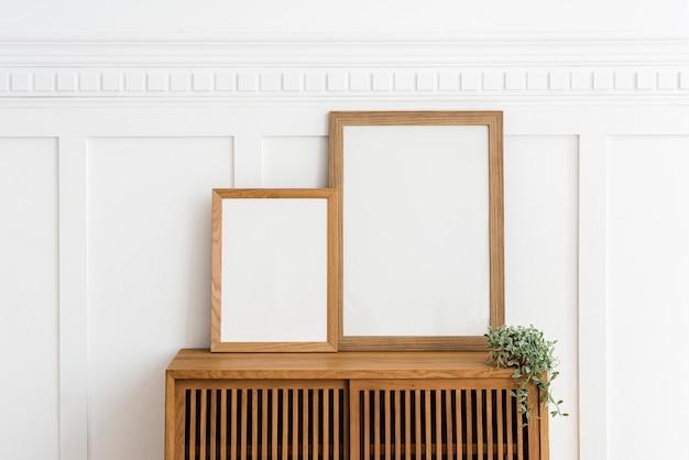 Twee fotolijsten op een houten dressoir