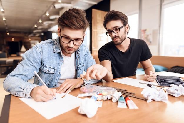 Twee freelancermensen die op papier met potloden bij bureau trekken.