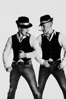 Twee gangsters met hoeden op en met een sigaar in hun mond kijken elkaar agressief aan. zwart en wit
