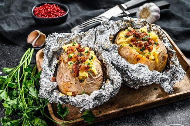 Twee gebakken aardappelen met spek, groene ui en kaas