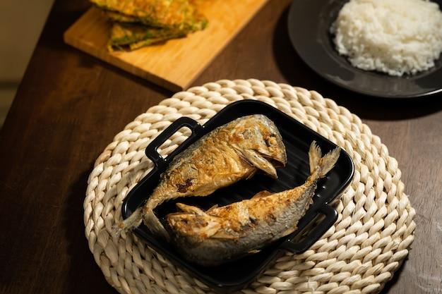 Twee gebakken korte makreel in een zwarte pan