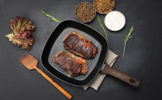 Twee gebakken stukjes rundvlees liggen in een koekenpan op een zwarte tafel, naast kruiden is de mate van bereidheid van het gerecht goed gaar