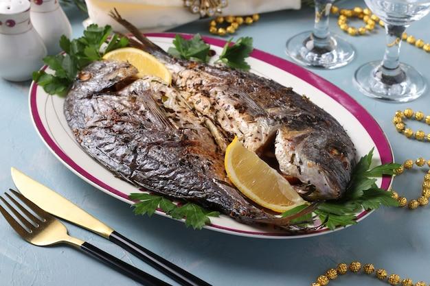 Twee gebakken vis dorado met kruiden serwed met peterselie en citroen op plaat op lichtblauw oppervlak