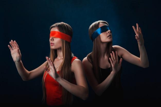 Twee geblinddoekte meisjes zoeken iets, rood en blauw lint, spel