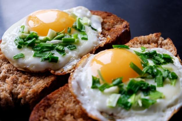 Twee gebraden eieren op brood het vullen de lente groene ui dicht omhoog
