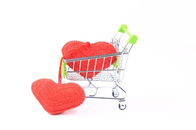 Twee gebreide harten in een winkelwagentje op een witte achtergrond. creatief valentijnsdagconcept