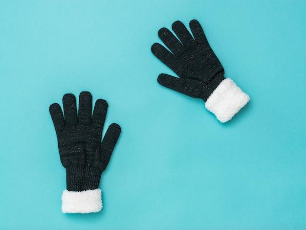 Twee gebreide zwarte dameshandschoenen op een blauwe achtergrond. winteraccessoires. plat leggen.