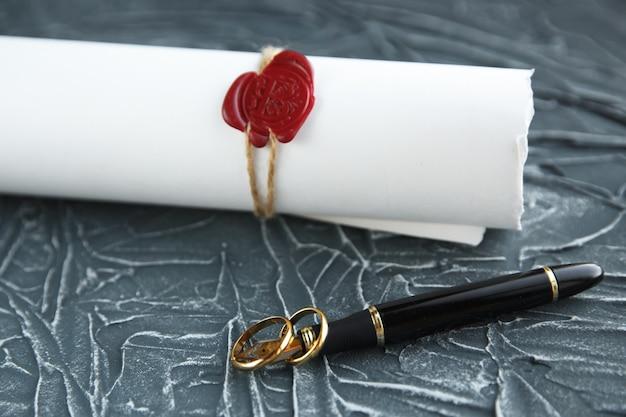 Twee gebroken gouden trouwringen echtscheidingsdocument. echtscheiding en scheidingsconcept